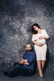 The happy young pregnant couple in the studio on a dark background. family relationship concept. royalty free stock photos