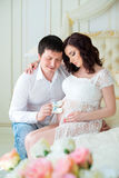 Happy young pregnant family in expectation of son, holding baby booties boys.  Royalty Free Stock Image