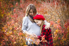 Happy young pregnant mother with daughter in autumn park. Happy young pregnant mother hugging with teen daughter in autumn park. Happy family concept royalty free stock photos