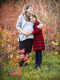 Happy young pregnant mother with daughter in autumn park. Happy young pregnant mother hugging with teen daughter in autumn park. Happy family concept stock photography