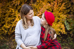 Happy young pregnant mother with daughter in autumn park. Happy young pregnant mother hugging with teen daughter in autumn park. Happy family concept royalty free stock images