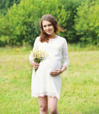 Happy young pregnant woman with chamomiles flowers Royalty Free Stock Images