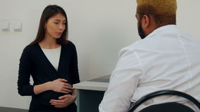 Happy young pregnant woman having a prenatal check up with male doctor stock video