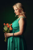 Happy young pregnant woman holding flowers Royalty Free Stock Photos