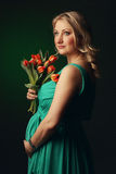 Happy young pregnant woman holding flowers Stock Photos