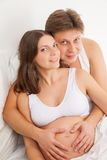 Happy young pregnant woman with husband on bed Stock Photography
