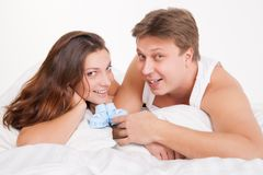 Happy young pregnant woman with husband on bed Royalty Free Stock Photography