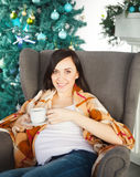Happy young pregnant woman siting in armchair Stock Photography