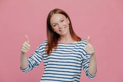 Happy young pretty European lady give double thumb up, likes somebody idea or gives approval, dressed in striped outfit, isolated royalty free stock photography