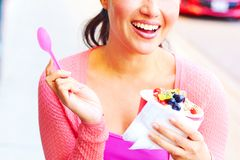Happy Young Pretty Mixed Race Female Eating Frozen Yogurt. Pretty happy young pretty mixed race female eating frozen yogurt while looking away. Horizontal Shot Stock Image