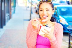 Happy Young Pretty Mixed Race Female Eating Frozen Yogurt. Pretty happy young pretty mixed race female eating frozen yogurt while looking away. Horizontal Shot Stock Photography
