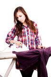 Happy young pretty woman ironing clothes Stock Images