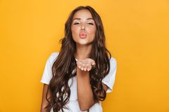 Happy young pretty woman posing isolated over yellow background blowing kisses. Image of happy young pretty woman posing isolated over yellow background blowing royalty free stock photography
