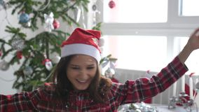 Happy young pretty woman in Santa cap throws up confetti near the Christmas tree by the window and shows the shape of stock video