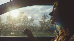 Happy young pretty woman sitting in car passenger looking out window on sunny day enjoying rural car ride. Trip Stock Image