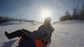 Happy young pretty woman is sledding in the mountain through the sun in slow motion on sunny day and recording themself. On video. 1920x1080. hd stock footage
