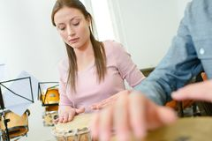 Happy young pretty woman smiling and playing bongos drum stock images