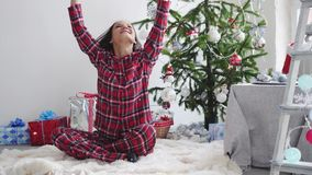 Happy young pretty woman throws up confetti near the Christmas tree by the window. slow motion. 3840x2160. Happy young woman throws up confetti near the stock footage