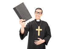 Happy young priest holding a holy bible Royalty Free Stock Photography
