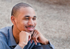Happy Young Professional African American Man. Close-up portrait of a smiling, young, professional Black man with his chin resting casually on his loosely closed Royalty Free Stock Image