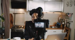 Happy young professional African female fashion blogger filming video blog using camera at home kitchen slow motion. Beautiful black woman working as a vlogger stock footage