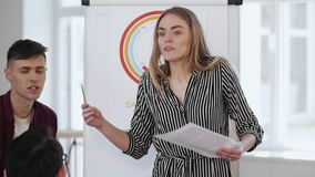 Happy young professional business woman leading team discussion at modern trendy office, explaining sales flipchart. Positive smiling female leader expert stock video
