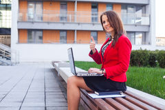 Happy young professional business woman sitting outdoor with com. Puter laptop. In the background office block Stock Photos