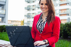 Happy young professional business woman sitting outdoor with com. Puter laptop. In the background office block Stock Images