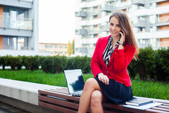 Happy young professional business woman sitting outdoor with mob. Ile phone. In the background office block Royalty Free Stock Images