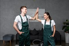 Happy young professional cleaning company workers smiling each other and giving high. Five stock photo