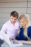 Happy, young professional couple using laptop Royalty Free Stock Photos