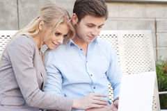 Happy, young professional couple using laptop Royalty Free Stock Image