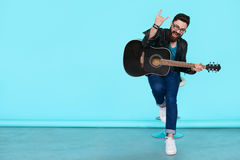 Happy young punk rocker with a guitar and dark sunglasses. On blue background. Full body man in leather jacket showing Rock sign with copy space Royalty Free Stock Photos