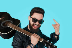 Happy young punk rocker with a guitar and dark sunglasses. On blue background. Man in leather jacket showing Rock sign Royalty Free Stock Image