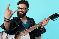 Happy young punk rocker with a guitar and dark sunglasses. On blue background. Man in leather jacket showing Rock sign Royalty Free Stock Photos