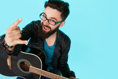 Happy young punk rocker with a guitar and dark sunglasses. On blue background. Man in leather jacket showing Rock sign with copy space Stock Photos