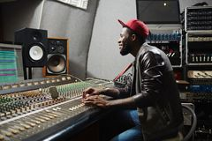 Sound mixing. Happy young rapper sitting by recording equipment in audio production studio Royalty Free Stock Photos