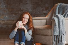 Happy young readhead woman drinking hot coffee or tea at home. Calm and cozy weekend in winter. Or autumn stock photo