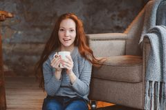 Happy young readhead woman drinking hot coffee or tea at home. Calm and cozy weekend in winter royalty free stock images
