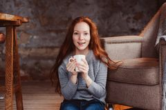 Happy young readhead woman drinking hot coffee or tea at home Stock Image