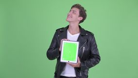 Happy young rebellious man thinking while showing digital tablet stock footage