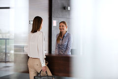 Happy young receptionist talking with businesswoman in office Stock Images