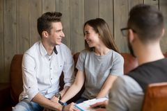 Happy young reconciled couple making up during counseling therap. Happy young reconciled couple making up at therapy session with psychologist, relieved smiling Royalty Free Stock Image
