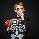 Happy young red hair boy with skeleton costume holding and eating colorful candies Royalty Free Stock Image