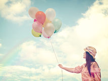 Happy young red hair woman  holding colorful balloons and flying on clouds sky background. Stock Photo