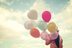 Happy young red hair woman  holding colorful balloons and flying on clouds sky background. Stock Image