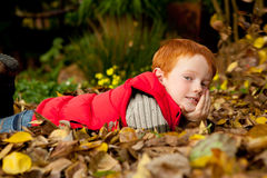 A happy young red haired boy is lying in a pile of Stock Photo