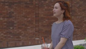 Happy young redhead woman drinking take away cold coffee wearing light striped dress in summer with brown brick wall in stock video footage