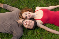 Happy couple in love laying down on the grass. Happy young relaxed couple in love laying down on the grass, high angle Stock Images