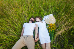 Happy young relaxed couple in love laying down on the grass overhead Royalty Free Stock Photography